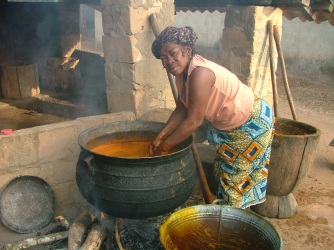 Iya prepares palm oil.