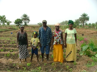 Members of a gardening collective pose in front of their land.